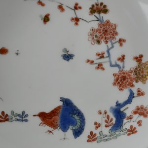 An 18th century Meissen Porcelain saucer decorated in the Kakiemon style c.1735-1745. Painted with a version of the 'Two Quail' design with a prunus tree and other flowers as well as insects. This Meissen porcelain saucer is quite close to the Japanese kakiemon porcelain orginal in terms of painting style as well as the enamel colours employed. However, the design has lost its asymmetry through being made more regular in form. This has resulted in the use of white space, that would have been an important element in the orginal Japanese composition, has had to give way to a design that is more evenly spread over the porcelain surface.