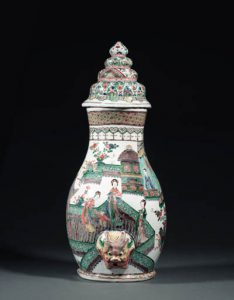 A RARE FAMILLE VERTE WALL FOUNTAIN AND COVER kangxi The pear-shaped body enamelled with elegant ladies in conversation on a terrace in front of pavilions below a ruyi-cloud collar and a trellis-pattern band at the mouth, the lower section modelled in relief with lion-mask spout, the domed cover with geometric and floral motifs in four registers, some restoration 22 in. (55.5 cm.) high