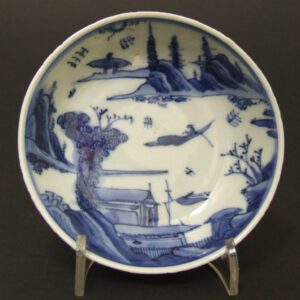 A Small Ming Blue and White Porcelain Dish, Early Wanli Period c.1580-1600. The Thinly Potted Porcelain Dish, Probably Made for the Japanese Market, was Part of a Set of 5 (For 3 other dishes from this set see `References` below). The Scene is Finely Painted in Strong Tones of Cobalt Blue, it Shows an Extensive Landscape Arranged Around Water. The Foreground has a Building with a Flag, the Center with a Small Craft on the Water. The Mountainous Landscape in the Background Contains Pagodas Among Trees.